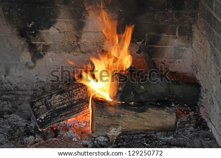 Three logs burning in an outdoor fire place - stock photo