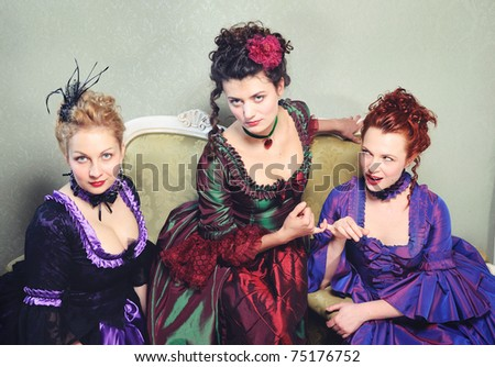Three lovely dames in ancient dresses sitting on a antique couch - stock photo