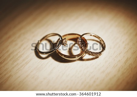 Three luxury platinum bridal rings on the leather surface, symbolizing love, togetherness and happy marriage. - stock photo