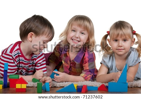 Three lying on the carpet children are playing blocks; isolated on the white background