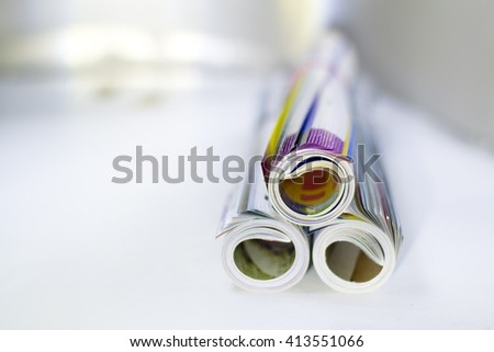 three magazine or brochure rolls kept on table with white blurry background. - stock photo