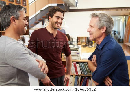 Three Male Architects Chatting In Modern Office Together - stock photo