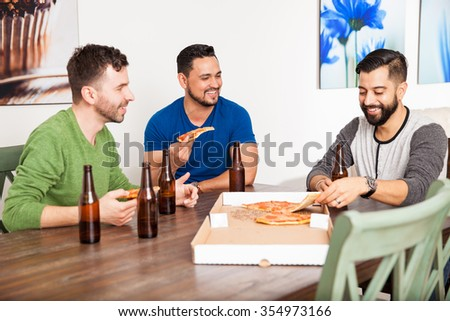 Three male Latin friends having fun at home while eating pizza and drinking some beer - stock photo