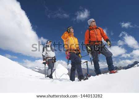 Three male mountain climbers reaching snowy peak against clouds - stock photo