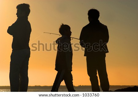 three males silhouetted against sunset sky fishing - stock photo