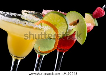 Three Margaritas - apple, orange and raspberry - in chilled glasses over black background. Most popular cocktails series.