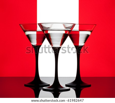 Three martini glass on a red-white-red background - stock photo