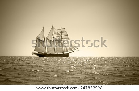 Three mast schooner under sails on the baltic sea. Sepia Toned. - stock photo