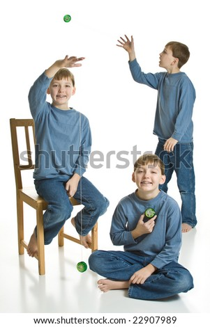 Three matching boys in blue playing with yo-yos. Isolated on a white background.