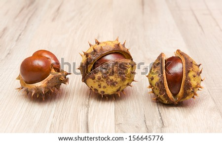 Three mature chestnut close-up on a wooden board. horizontal photo. - stock photo