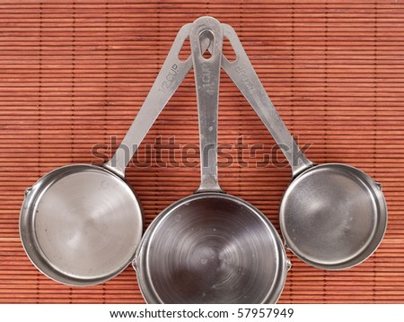 Three Measuring Cups on Bamboo Wood Mat - stock photo