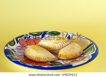 Three meat-filled Panama style empanadas on colorful platter against faded yellow background.