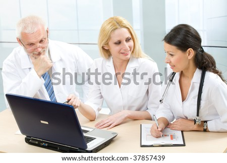Three medicine workers discuss computer work