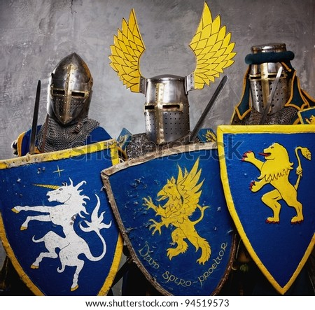 Three medieval knights  on grey background. - stock photo