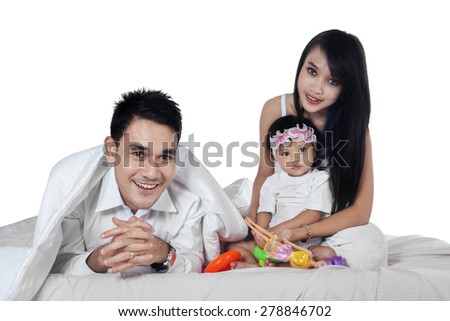 Three member of happy family playing together on bed, isolated on white background - stock photo