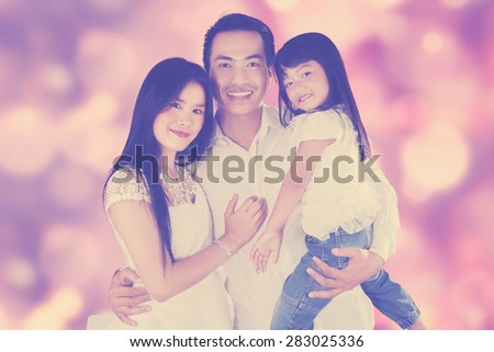 Three member of happy family smiling at the camera, shot with festive light background - stock photo