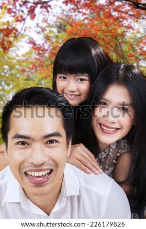 Three member of little happy family smiling on camera under autumn tree - stock photo