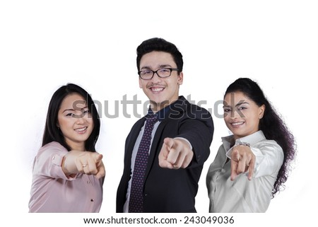 Three members of attractive entrepreneurs smiling and pointing at camera, isolated on white background - stock photo