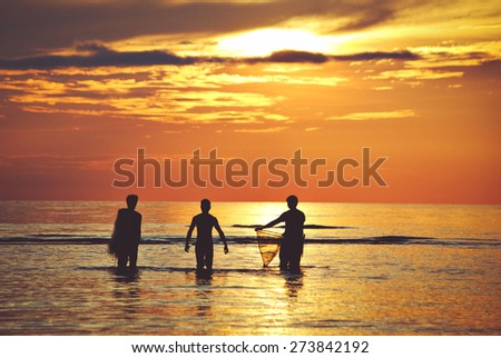 Three men carrying fishing equipments walking towards the sea during sunset. Image uses selective focusing and in faded Instagram effect for retro style background.