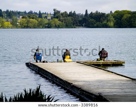 Three men fishing on a dock in the park. - stock photo