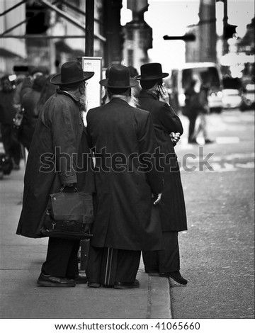 Three men in black coats waiting for NYC bus - stock photo