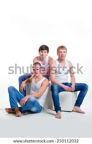 Three men in white shirts and jeans in the studio.