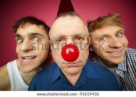 Three men of different age looking at camera, fool�s day celebration - stock photo
