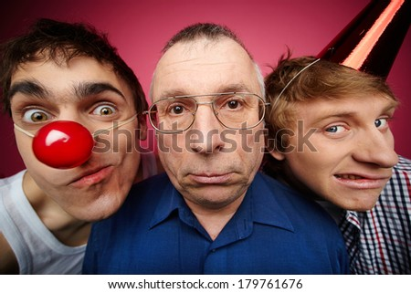 Three men of different age looking at camera, fools day celebration