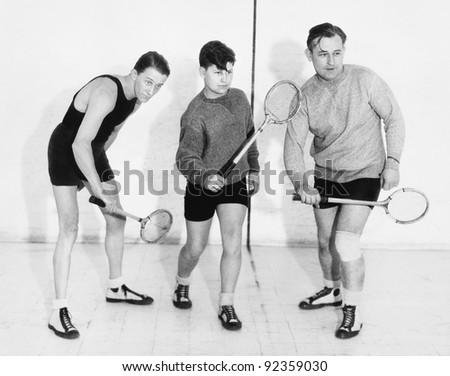 Three men playing squash - stock photo