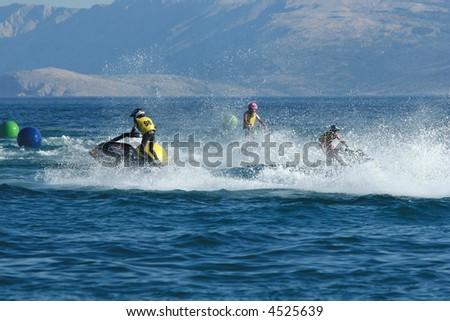 Three men racing on jet ski - stock photo