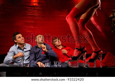 Three men sitting in front of dancing woman. They are looking confused and shocked. Front view - stock photo
