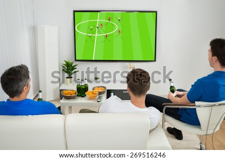 Three Men Sitting On Couch Watching Football Match On Television - stock photo