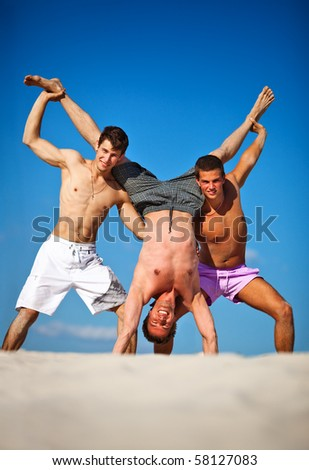Three men summer vacation on beach. - stock photo