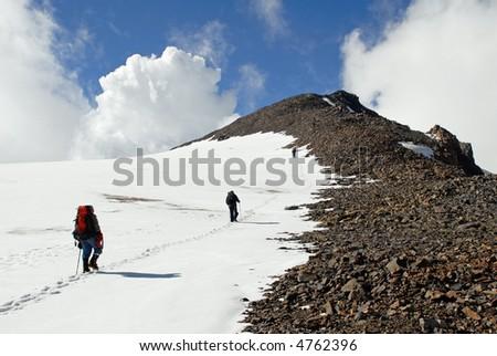 Three men trekking  on a mountain - stock photo