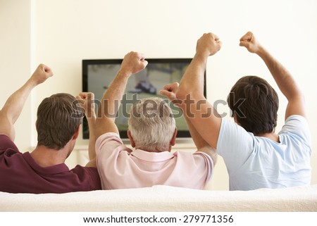 Three Men Watching Widescreen TV At Home - stock photo