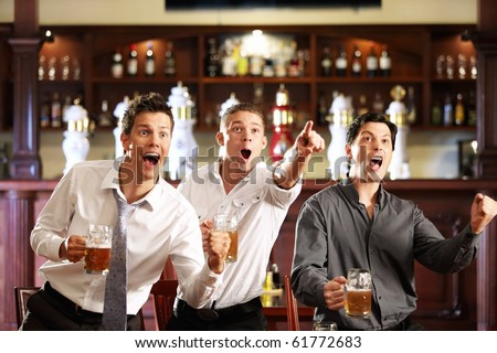 Three men with beer rejoice the victory of their favorite team in the pub - stock photo