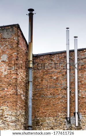 three metal chimneys, one old and rusty and two new and shiny attached to a shabby brick wall of an old building - stock photo