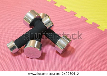 Three metal dumbbells on a floor in a gym. - stock photo
