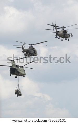three military helicopter in formation