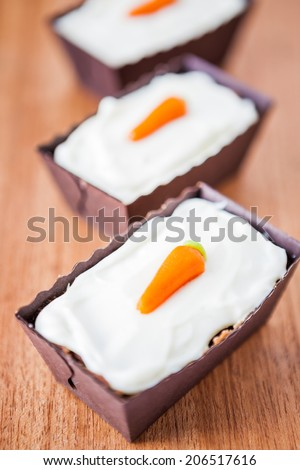 Three mini carrot cakes with mascarpone icing - stock photo