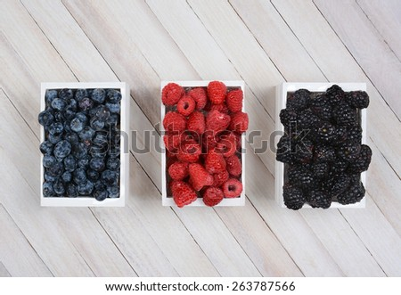 Three mini wood crates of berrie on a rustic wood surface. Blueberries Raspberries and Blackberries in small white boxes shot from a high angle.  - stock photo