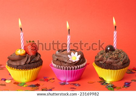 Three miniature chocolate cupcakes decorated with icing and burning birthday candles on red background