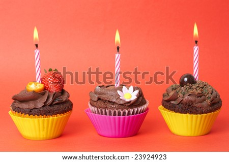 Three miniature chocolate cupcakes with icing, decorations and birthday candles on red background