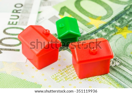three miniature plastic houses laying on one hundred euro banknotes - stock photo