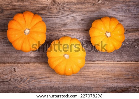 Three miniature pumpkins over old wood background. - stock photo