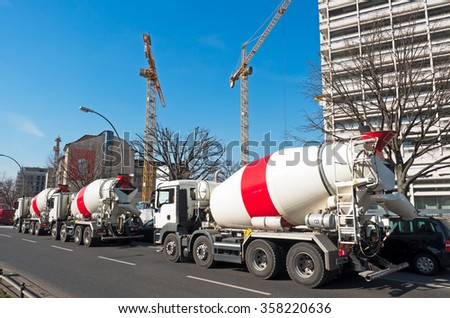 three Mixer Trucks on a street in town - stock photo