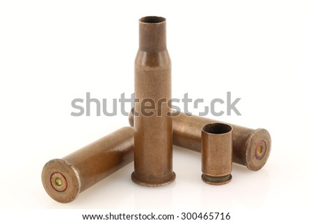 Three 7.62 mm caliber rifle and one 9 mm caliber pistol old bullet casings on a light background with slight mirror reflections on a background surface. Focus on full depth. - stock photo