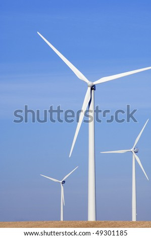 three modern windmills with clear blue sky