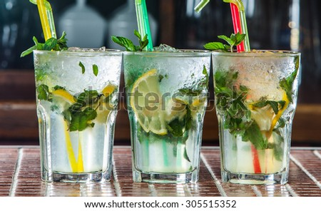 Three Mojito cocktails on a bar counter.Fresh mojito cocktails. Mojito cocktails on the background of the bar - stock photo