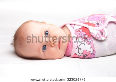 Three month baby girl wrapped in a modern winged baby swaddle laying on a bed - stock photo